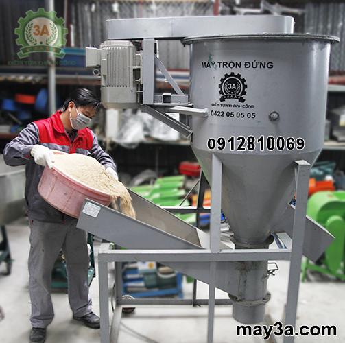 Kỹ thuật viên cho cám vào cửa nạp nguyên liệu của Máy trộn cám 3A5,5Kw