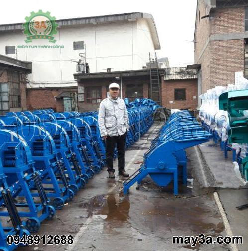 Nhà sáng chế Nguyễn Hải Châu bên cạnh hàng máy băm ván bóc 3A đang hoàn thiện (bên phải)