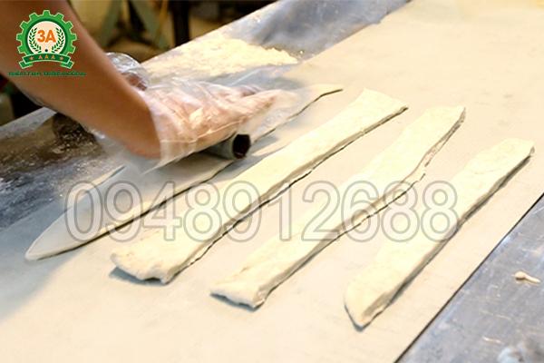 Nhiều dải bột được xếp lên băng tải của Máy thái quẩy 3A