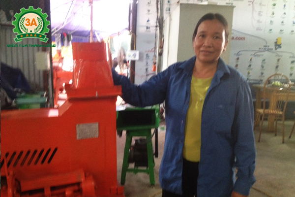 Cô Bùi Thị Ỏn bên cạnh chiếc máy băm cỏ 3A4Kw (3 pha)