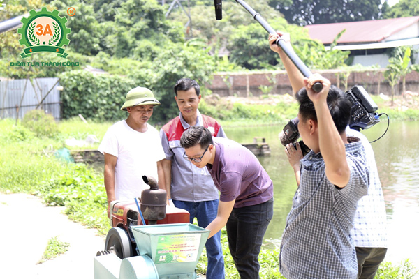 Phóng viên VTV cùng nhà sáng chế Nguyễn Hải Châu bàn giao máy ép cám viên nổi cho bà con